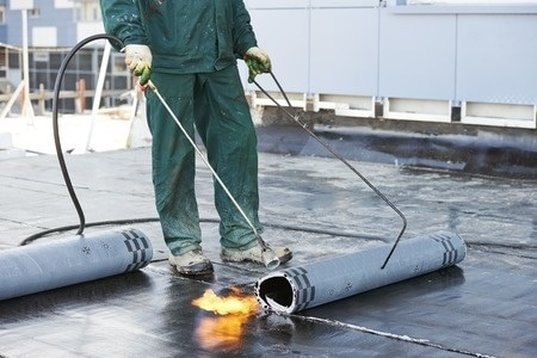 Rolling out bitumen torch down flat roofing Vaughan
