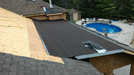 Looking at a home in Kitchener with a combination flat roof and shingle roof.